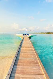 Pilastro di legno con il piccolo spazio di sosta dal mare blu tropicale, composizione verticale