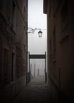 Pilastro di legno e vecchia posta della lampada in un giorno nebbioso a venezia, italia