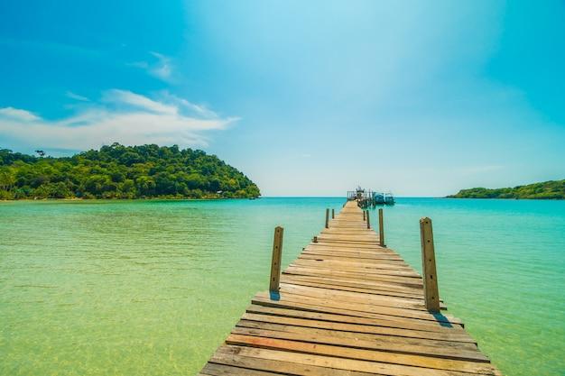 Pilastro di legno o ponte con spiaggia tropicale e mare nell'isola di paradiso