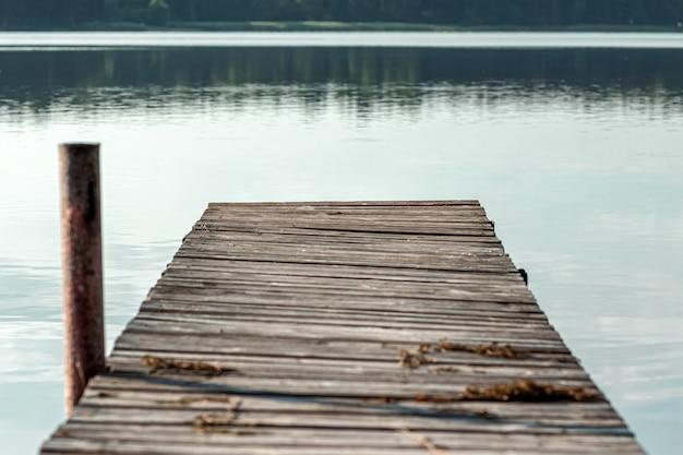 Pilastro di legno sul bellissimo paesaggio di alba estiva del lago. copia spazio.