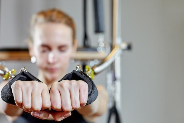 Pilates della donna della palestra che allungano sport nella ragazza dell'istruttore del letto del riformatore. messa a fuoco selettiva sulle mani