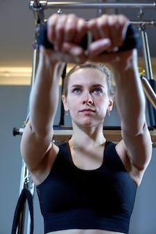 Pilates della donna della palestra che allungano sport nella ragazza dell'istruttore del letto del riformatore.