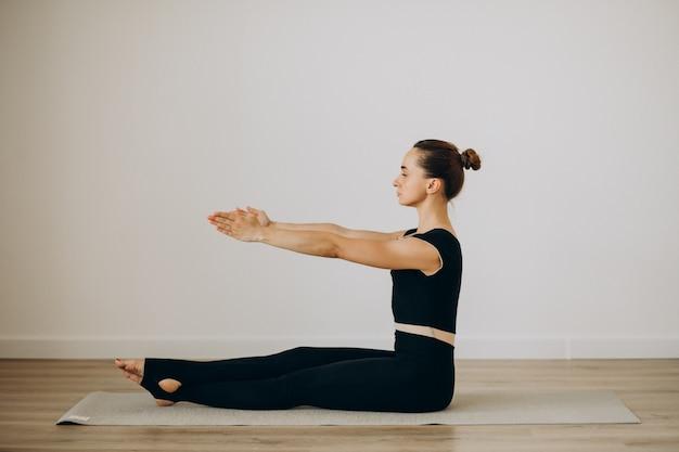 Pilates di pratica della donna alla palestra di yoga