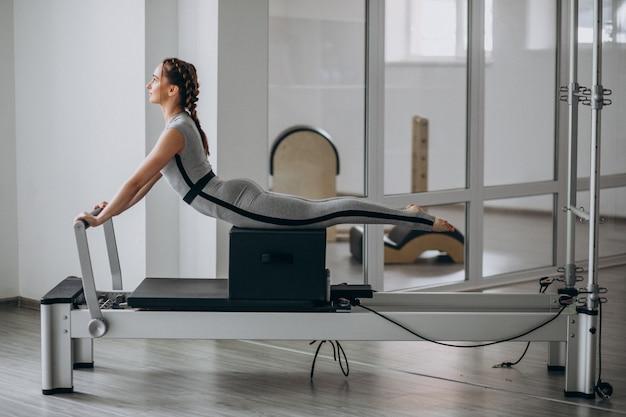 Pilates di pratica della donna in un riformatore dei pilates