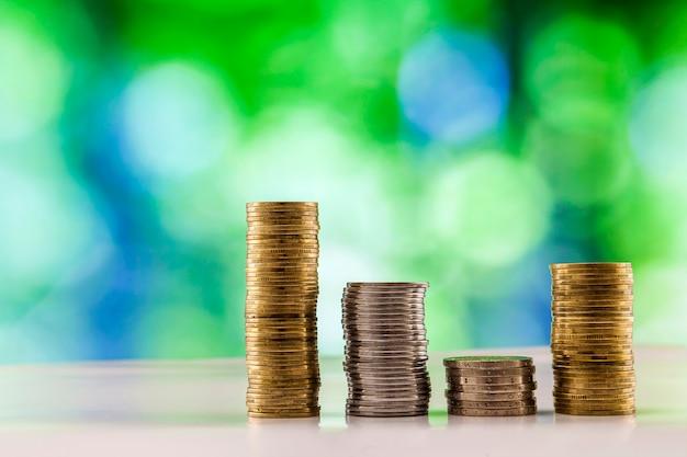 Pile crescenti delle monete con le luci scintillanti verdi e blu del bokeh