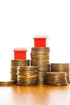 Pile di monete, casa verde e rossa. concetto di ipoteca dalla casa dei soldi dalle monete