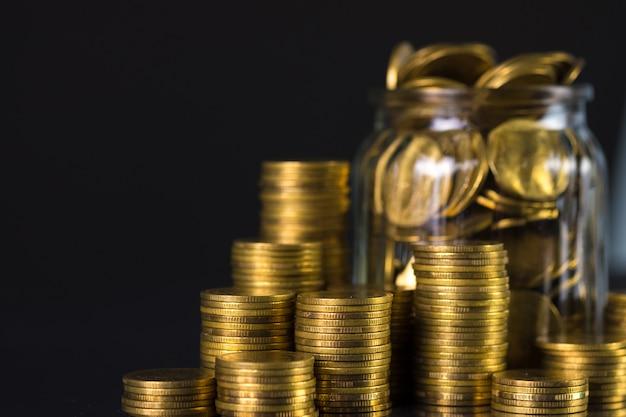 Pile di monete e monete d'oro nel barattolo di vetro su sfondo scuro, per il risparmio per il futuro concetto di finanza bancaria.