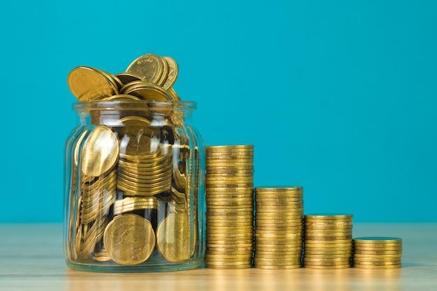 Pile di monete e monete d'oro nel barattolo di vetro sul tavolo