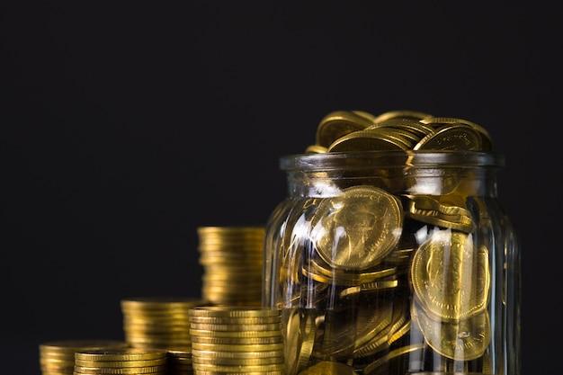 Pile di monete e monete d'oro nel barattolo di vetro