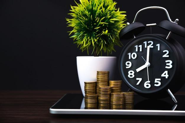 Pile di monete e sveglia con computer tablet e grafico finanziario