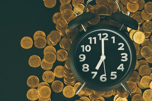 Pile di sveglia e monete sul tavolo di lavoro