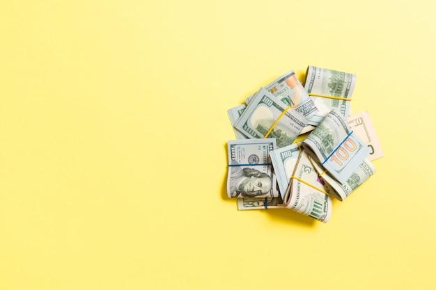 Pile di un primo piano di cento dollari di banconote sulla vista superiore di affari colorati del fondo con copyspace