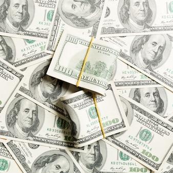 Pile di un primo piano di cento dollari di banconote sulla vista superiore di affari del dollaro con copyspace