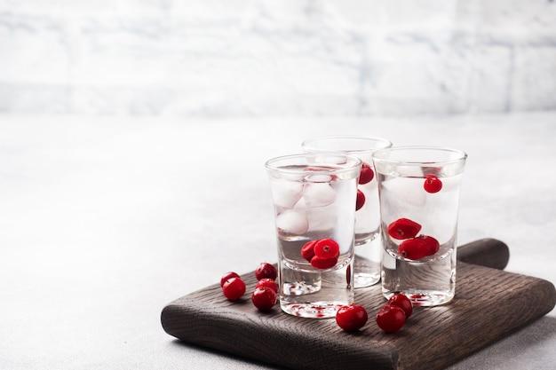 Pile di vodka e mirtilli rossi su un supporto di legno