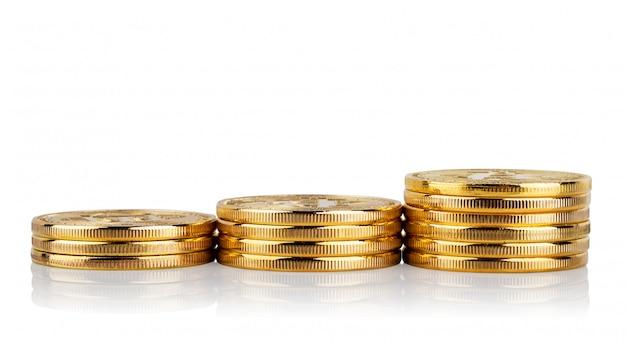 Pile in aumento di monete isolate sulla parete bianca
