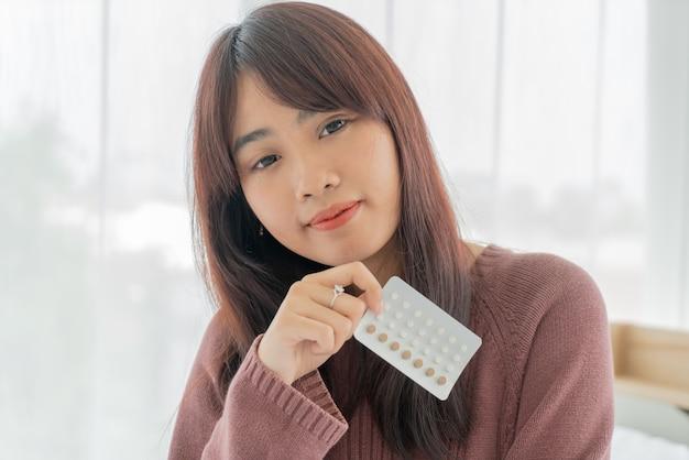 Pillola asiatica del controllo delle nascite della tenuta della donna