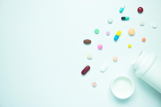 Pillola della medicina e bottiglia di plastica su fondo bianco
