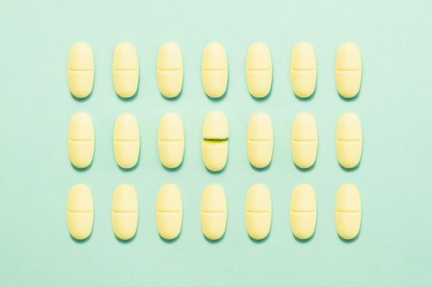 Pillola della medicina rotta a metà tra intere compresse sulla parete verde