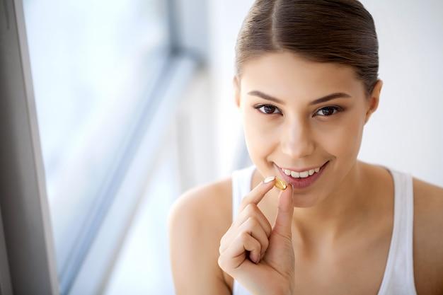 Pillola della tenuta della bocca della bella donna per i denti. ragazza che cattura vitamine