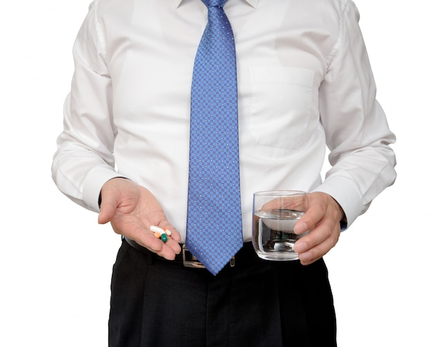 Pillola e tazza di acqua della tenuta dell'uomo d'affari a disposizione.