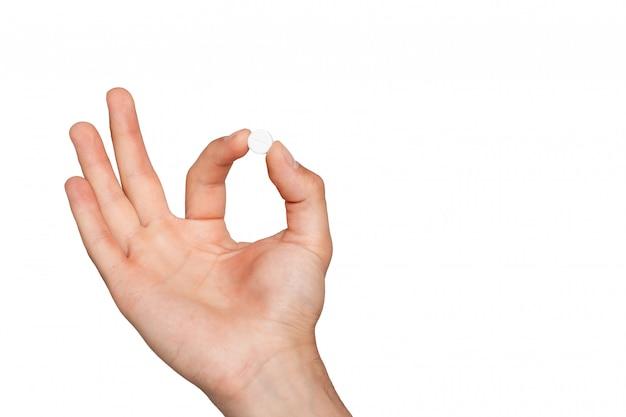 Pillola in mano dell'uomo su bianco