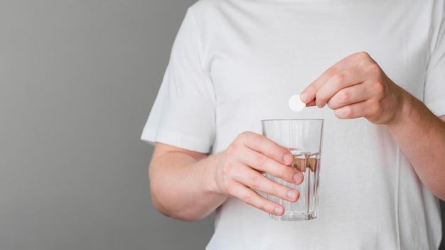 Pillola mettente paziente del primo piano in acqua