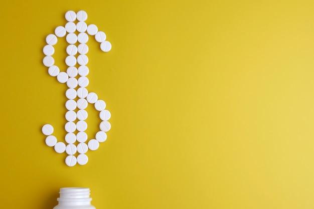 Pillola. pillole bianche su uno sfondo giallo sotto forma di un segno di dollaro da un vaso bianco