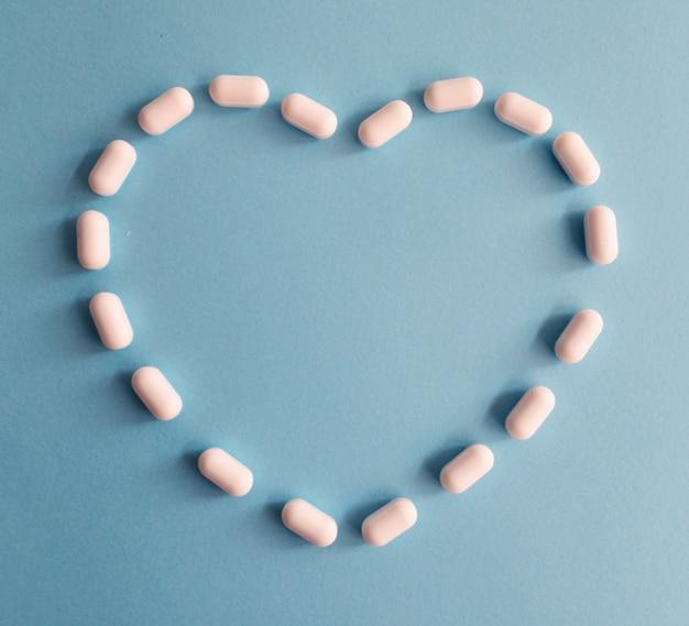 Pillole a forma di cuore su uno sfondo blu
