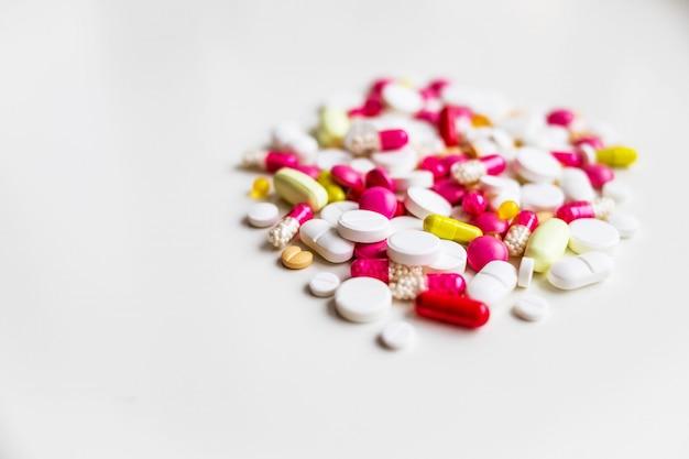 Pillole antibiotiche rosse, rosa e bianche su fondo verde