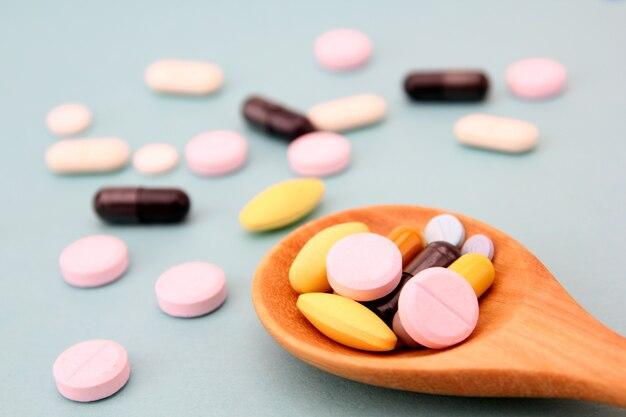 Pillole assortite, compresse e capsule della medicina farmaceutica sul cucchiaio di legno.