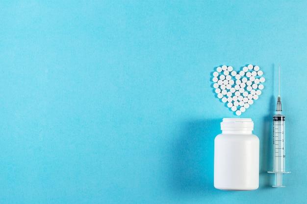 Pillole bianche a forma di cuore con bottiglia su sfondo blu.
