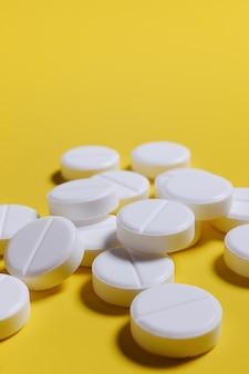 Pillole bianche, antidolorifici su uno sfondo giallo.