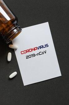 Pillole bianche che si rovesciano da una bottiglia marrone rovesciata e da un libro bianco con iscrizione. concetto di trattamento del coronavirus.