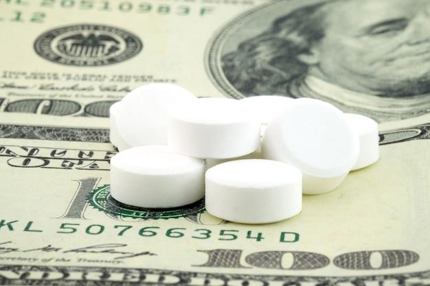 Pillole bianche e soldi, concetto di spesa sanitaria