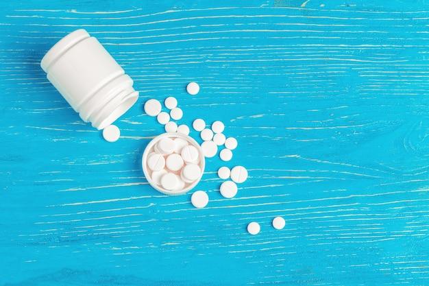 Pillole bianche rovesciate da un contenitore bianco
