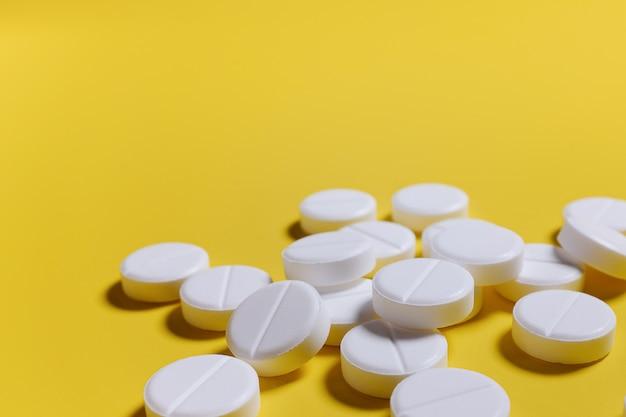 Pillole bianche su uno sfondo giallo. il concetto di medicina, farmacia e salute.
