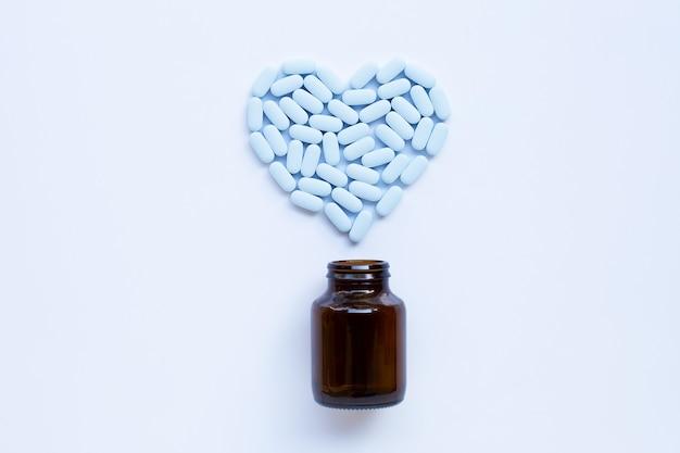 Pillole blu che formano una forma di cuore sulla bottiglia