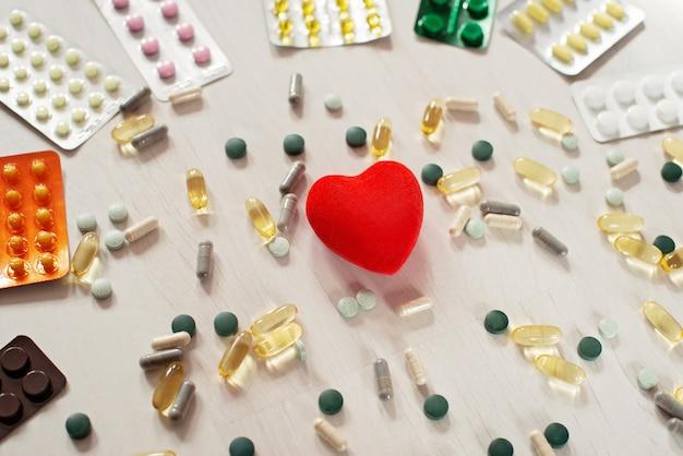 Pillole capsule con pillole antibiotiche medicinali, capsule di olio di pesce e cuore rosso