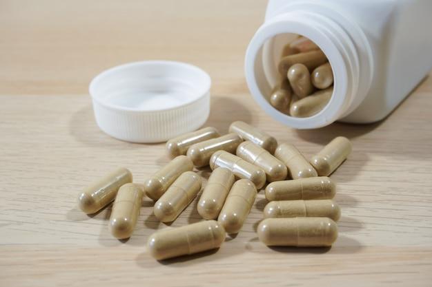 Pillole che si rovesciano dalla bottiglia bianca