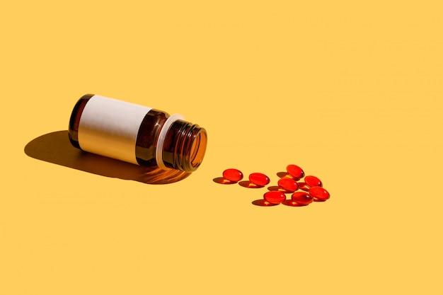 Pillole che si rovesciano dalla bottiglia di pillola che forma un segno della freccia su giallo