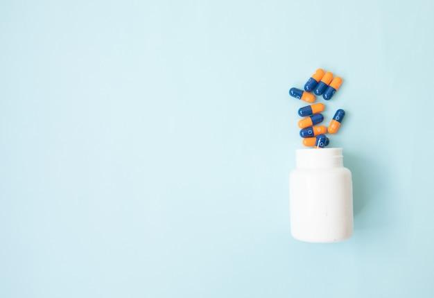 Pillole che si rovesciano dalla bottiglia di pillola e isolate sul blu. vista dall'alto con spazio di copia.