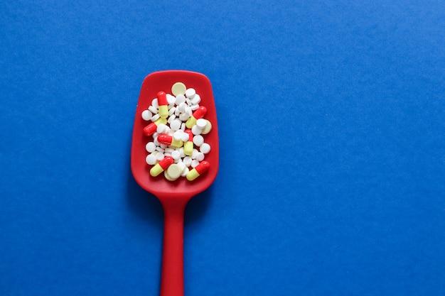 Pillole, compresse e capsule della medicina farmaceutica sul cucchiaio di plastica.