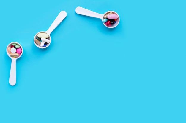 Pillole, compresse e capsule variopinte della medicina sul blu