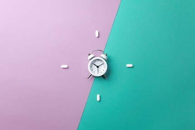 Pillole, compresse e sveglia bianca su verde e viola