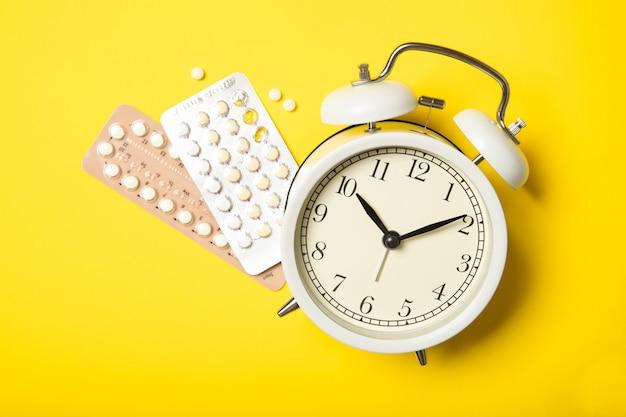 Pillole contraccettive e sveglia su uno sfondo giallo