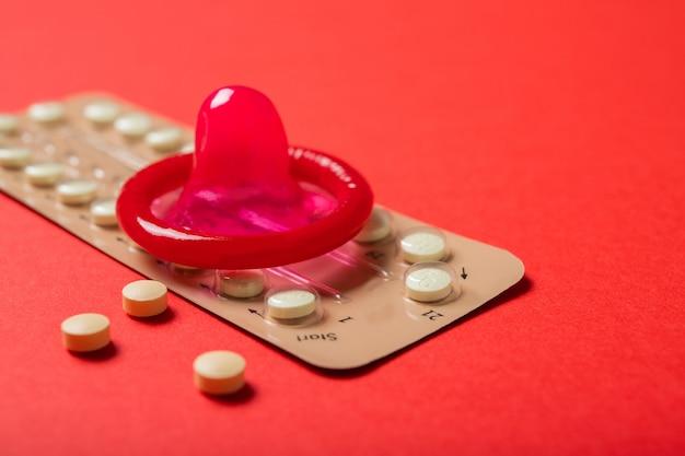 Pillole contraccettive e un preservativo su uno sfondo rosso
