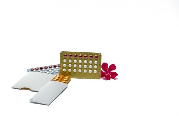 Pillole contraccettive o pillole anticoncezionali con fiore rosa su sfondo bianco con spazio di copia. ormone per la contraccezione. concetto di pianificazione familiare. compresse ormonali rotonde bianche e rosse in blister