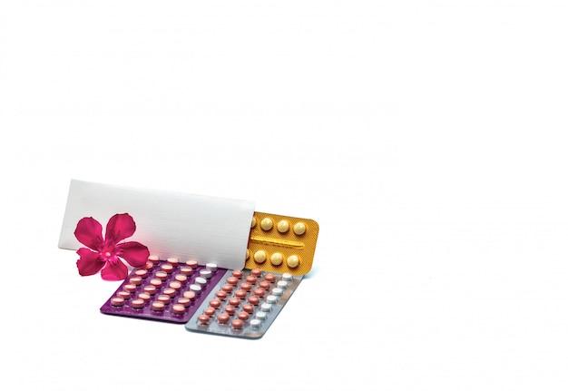 Pillole contraccettive o pillole anticoncezionali con fiore rosa su sfondo bianco con spazio di copia. ormone per la contraccezione. concetto di pianificazione familiare. compresse ormonali rotonde in blister.
