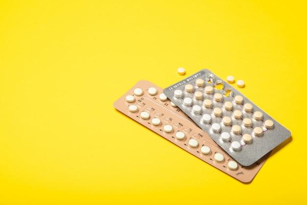 Pillole contraccettive su uno sfondo giallo
