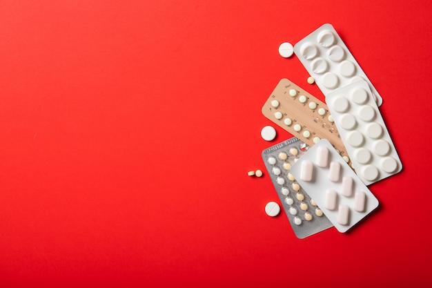 Pillole contraccettive su uno sfondo rosso